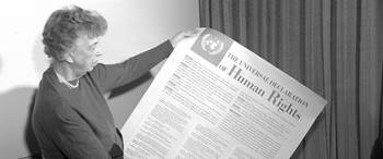 Mrs. Eleanor Roosevelt of the United States holding a Universal Declaration of Human Rights poster in English.